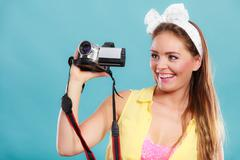 Happy pin up girl woman filming with camcorder. - stock photo