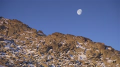 Moon over stone hill covered with snow Stock Footage