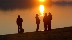 silhouettes of people on the river bank - stock footage