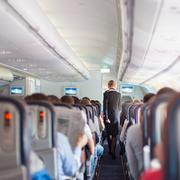 Stewardess and passengers on commercial airplane. - stock photo