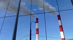 Pipes with a smoke and reflection in a glass building, Russia Stock Footage