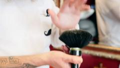 A barber is taking the powder away from his brush Stock Footage