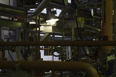 abstract interior of the plant: pipes valves, steel construction - stock photo