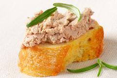 Slice of crunchy baguette with chicken liver pate - stock photo