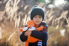 Cute little caucasian child, boy, holding fluffy toy, hugging it, in the park - stock photo