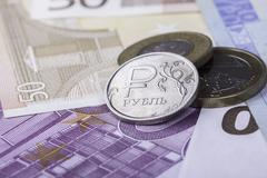 Coin ruble against the background of Euro banknotes Stock Photos