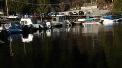 Still water surface, boats tied up to dock Stock Footage