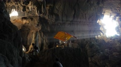 Sun rays shining in Tham Phu Kham cave with tourists ,Vang Vieng,Laos Stock Footage