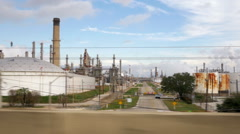Slow motion driving past a large oil refinery Stock Footage