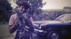 1969: Boy holding 2 lost kitty cats that he found with his camero car. DES Stock Footage