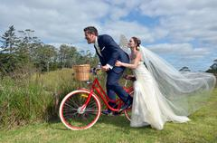 Husband and wife ride on bicycle on their wedding Day - stock photo