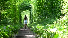 Young slim teenager girl walks away from camera in natural green forest Stock Footage