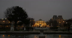 Arc de Triomphe du Carrousel and Louvre seen through Grand Basin Rond in Stock Footage