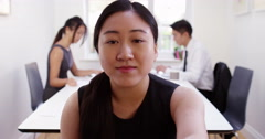 An Asian manager having a video conference from her boardroom. Shot on RED Epic. - stock footage