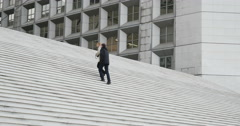 Couple climbing and admiring La Defense stairs and monument, Paris, France Stock Footage