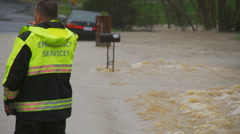 Emergency Services crew surveys flooded road Stock Footage