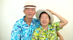Happy Asian senior couple with victory sign and thumb up ready for holiday trip - stock footage