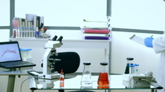Scientist walks in and works with a microscope in laboratory - stock footage