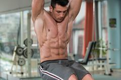 Young Man Performing Hanging Leg Raises Abs Exercise - stock photo