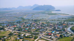 High veiw of shrimp farm in pond  with village along sea Stock Footage