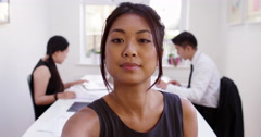 Happy young Asian manager having a video conference from her boardroom. - stock footage