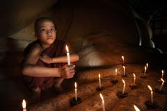 Buddhist novice with candlelight Stock Photos