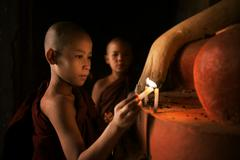 Buddhist novices praying with candlelight in monastery - stock photo