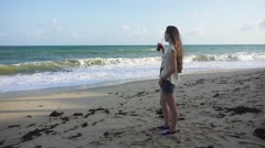 Girl Drinking a Refreshing Drink from Glass Bottle While Standing on the Beach Stock Footage