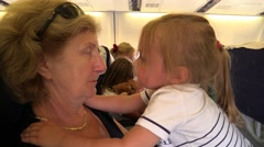 Little girl play with grandmother in the plane cabin. Slow Motion Stock Footage