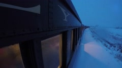 Exterior shot of a train going through snowy fields in storm Stock Footage