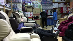 One side of people enjoying massage chair inside Crystal mall Stock Footage
