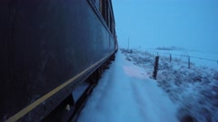 Exterior shot of train going through snowy fields Stock Footage