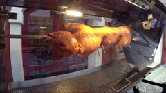 Rotisserie close up of small pig animal is skewered on spit long solid rod 4k Stock Footage