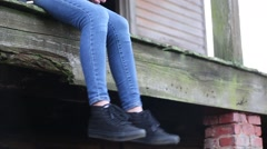 Isolated Shot of Teen Girl Legs Swinging off Porch of Abandoned House Stock Footage