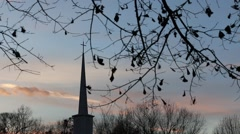 Stock Video Footage of Church Steeple in Glorious Sunset Seen Through Wintry Leaves