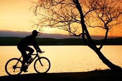 Young man cyclist silhouette on pink orange sky and sunset background on the  Stock Photos