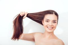 Beautiful Asian girl holds her hair in hands. Naked shoulders - stock photo