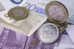 Coin one ruble and the European currency: banknotes, euro coins Stock Photos