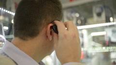 Man attaches to the ear bluetooth device Stock Footage
