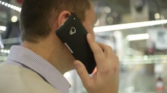 Man speaking talking to the mobile phone - view from back Stock Footage