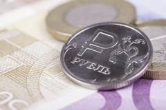 coin ruble against the background of Euro banknotes - stock photo