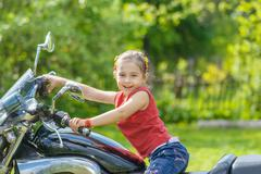 Little cheerful girl on old bike - stock photo