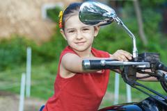 Stock Photo of Little cheerful girl on old bike
