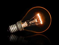 Light Bulb with awesome glare and reflection isolated against black backgroun Stock Photos