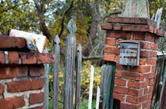Very old rusty post box on the brick column. Kuvituskuvat
