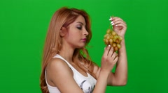 Seductive Woman Eating Grapes on Green Screen - stock footage