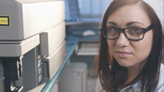 Portrait of confident female scientist using in lab tech loading samples into a Stock Footage