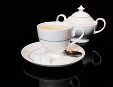 Cup of coffe and sugar bowl on black background Stock Photos
