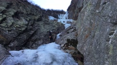Ice climbing: climber abseiling back down on a icefall using a double rope. - stock footage