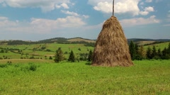Clouds and haystack on green field Stock Footage